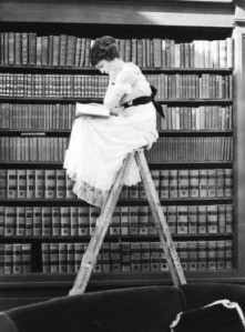 Woman Reading on Top of Ladder © Bettmann/CORBIS